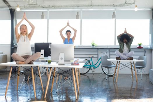 Executives doing yoga in office