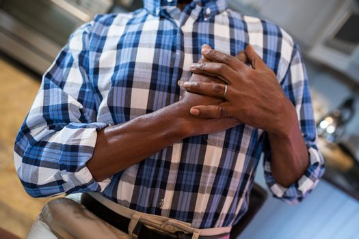 Midsection of man with hand on chest suffering from chest pain