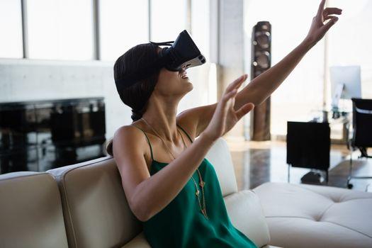 Woman using virtual reality simulator at office