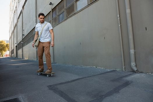Young man skating on footpath by building