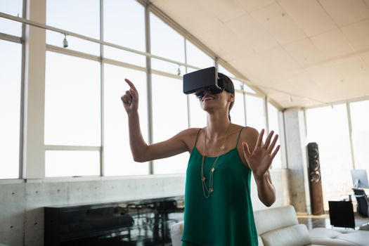 Businesswoman using virtual reality simulator in office