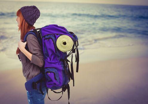 Millennial backpacker on blurry beach