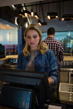 Woman using cash register at bar