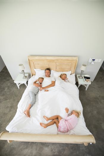 Family sleeping on bed in the bed room