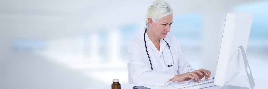 Doctor at computer against blurry window