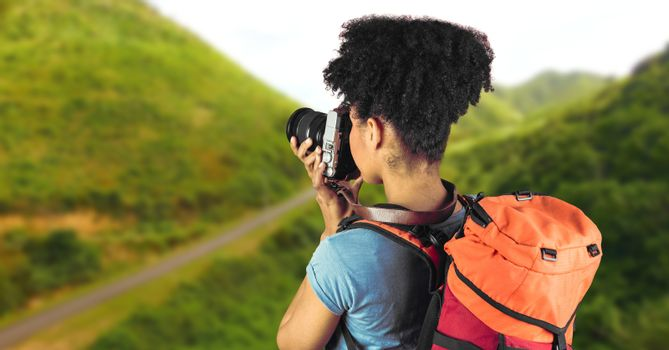 Millennial backpacker with camera against blurry grassy hills