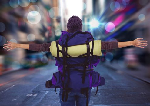 Back of millennial backpacker arms outstretched against blurry street with flares and bokeh