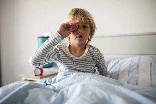 Boy rubbing his eyes in the bedroom
