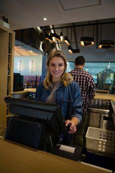 Portrait of female owner using cash register at bar