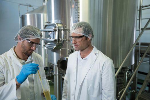 Coworkers examining beer