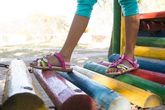 Girl wearing sandal walking on jungle gym