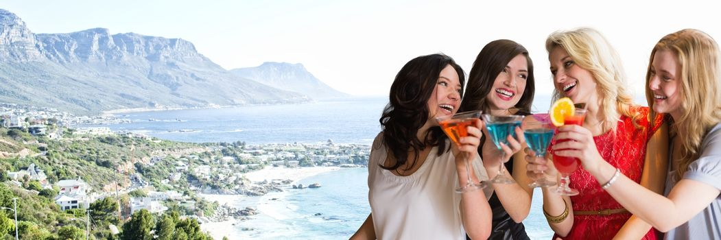 Women with cocktails against blurry coastline