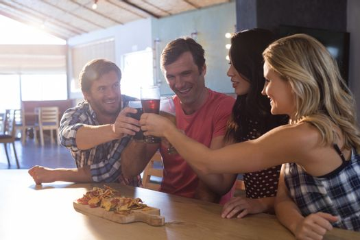 Friends enjoying food and drink while standing at bar counter