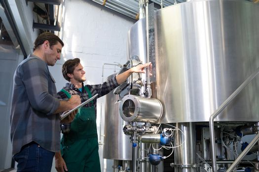 Man explaining to coworker at brewery