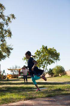 Friends running jumping on grassy field