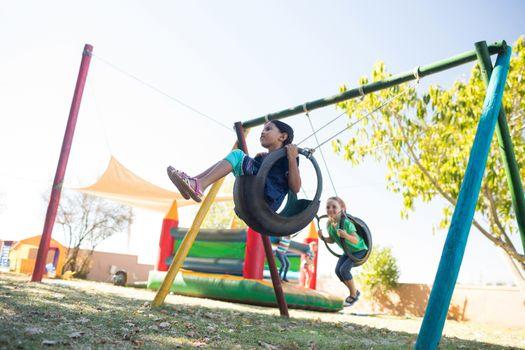 Girls swinging at playground against sky