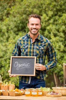 Portrait of man with blackboard selling vegetables