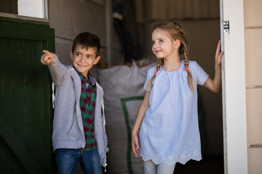 Boy and girl talking at each other in the stable