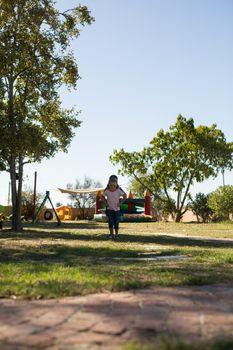 Girls jumping on grassy field at playground