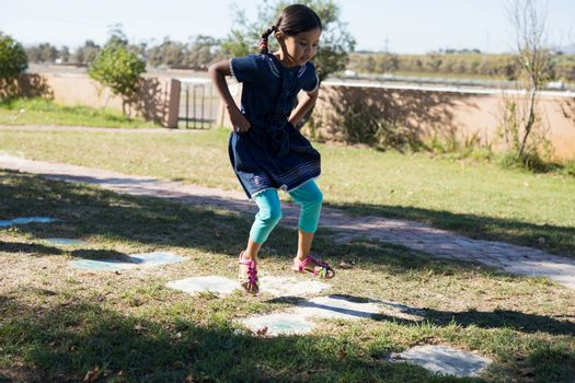 Girl with hands on hip jumping on grassy field