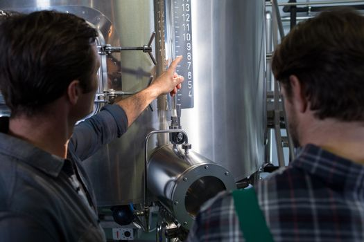 Worker explaining to coworker at brewery