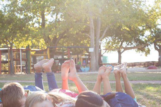 Happy children relaxing on grassy field at park