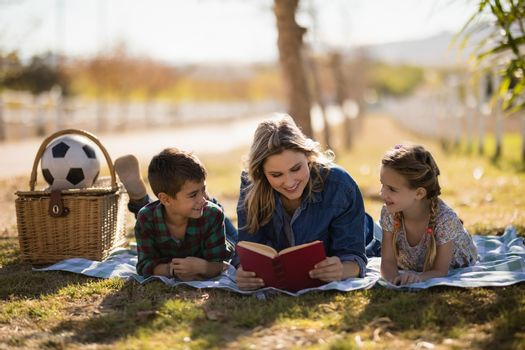 Mother and kids reading novel in park