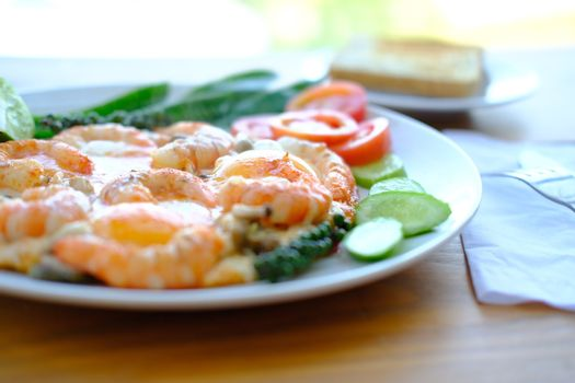 Delicious breakfast Fried eggs with prawns decorate fresh vegetables and toast, asian style food. Selective focus close up.