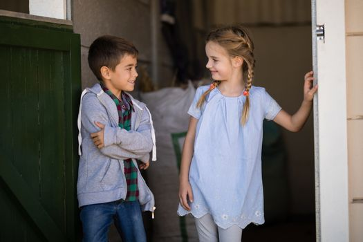 Boy and girl smiling at each other in the stable
