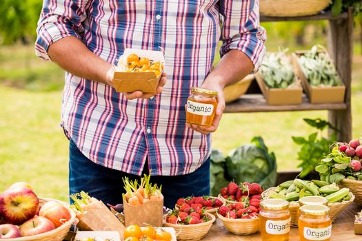 Midsection of man selling tomatoes and preserves