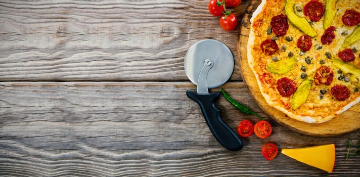 Pizza on by cutter on wooden table