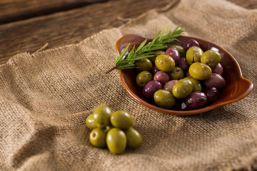 Marinated olives with herbs on burlap