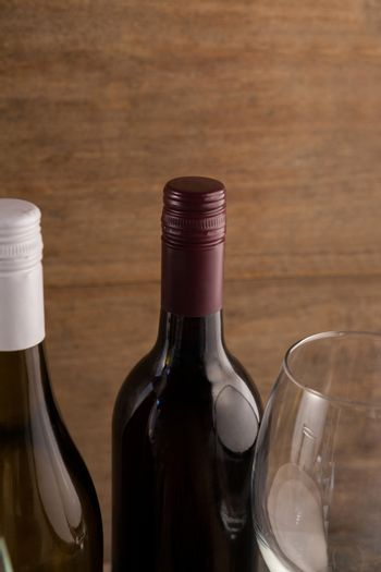Cropped image of wineglass by bottles