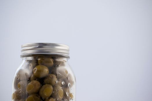 Green olive in glass jar with silver lid