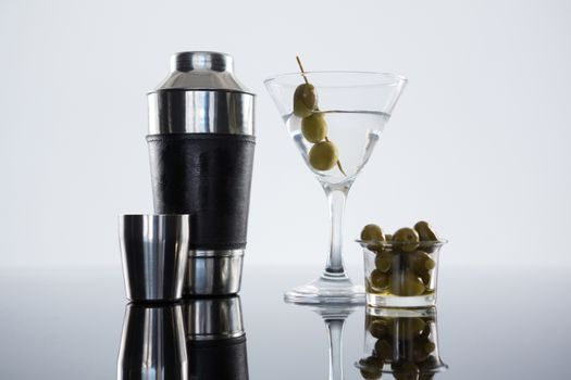 Cocktail martini with olives and shaker on table