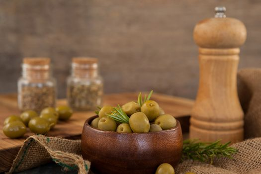 Olives and rosemary in bowl by pepper shaker