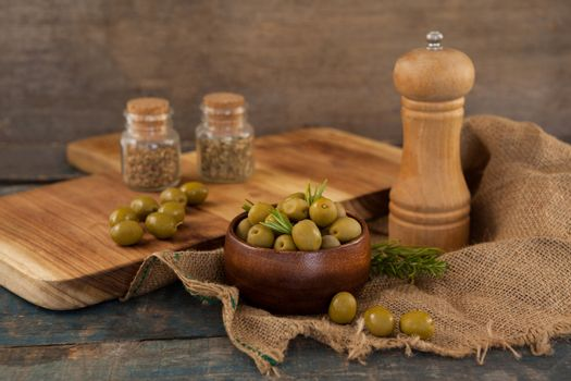 Olives in bowl by pepper shaker on burlap