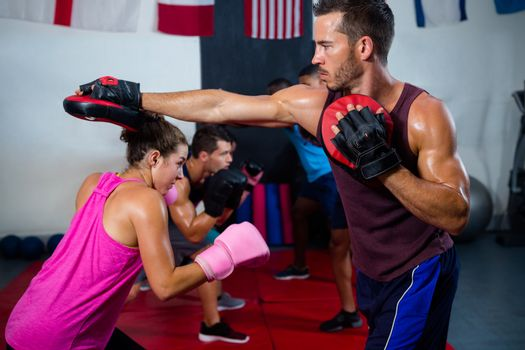 Female boxer defending with instructor