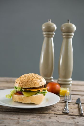Hamburger in plate by pepper shaker on table