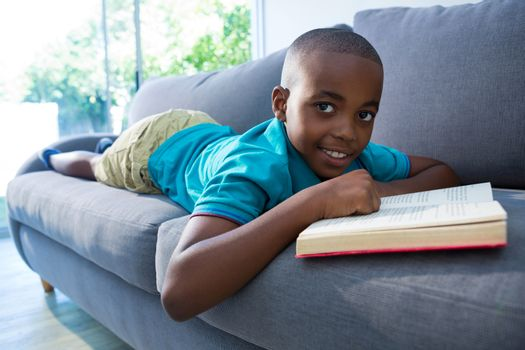 Boy lying on sofa with novel at home