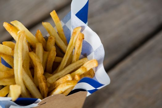 Close up of French fries with wax paper in container