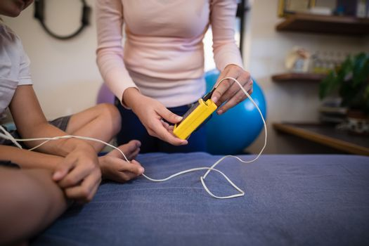 Midsection of female therapist showing electrical muscle stimulation machine to boy sitting on bed