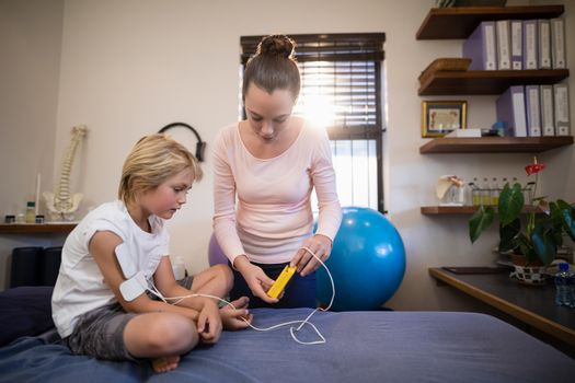 Female therapist showing electrical muscle stimulation machine to boy sitting on bed
