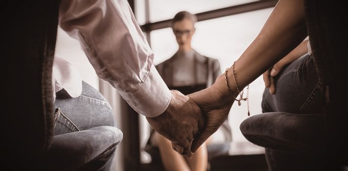 Couple holding hands with marriage counselor