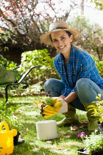 Portrait of smiling woman planting seedling