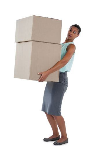 Businesswoman carrying heavy boxes