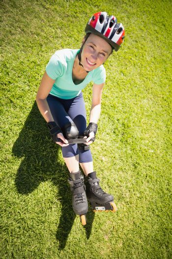 Fit mature woman in roller blades on the grass