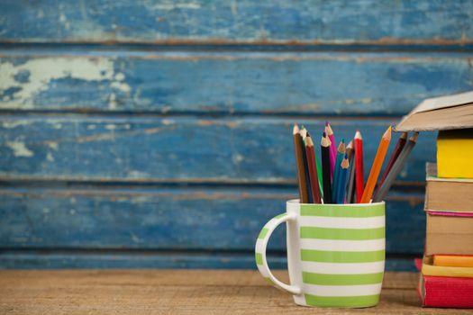 Pen holder against blue wooden background