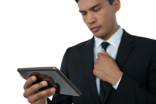 Businessman holding necktie while using tablet computer