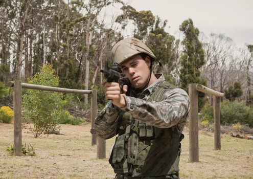 Soldier man holding a weapon against field